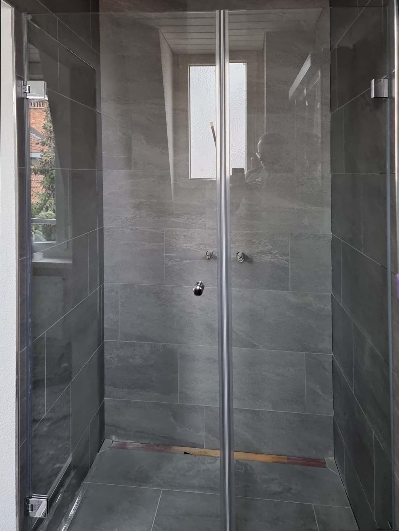 Glastür in einer 3-seitigen Dusche